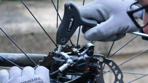Mécanicien vélo réajustant son étrier de frein VTT