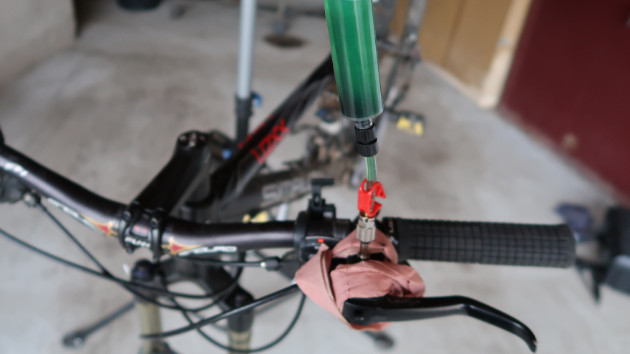 Le mécanicen repousse le piston de la seringue pour remplir le maître cylindre du frein Magura Louise