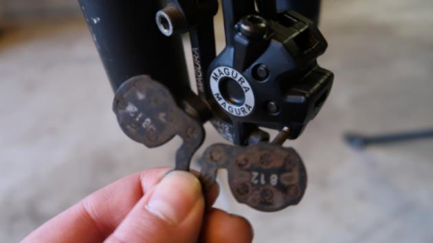 Mécanicien tenant des plaquettes VTT Magura pour montage