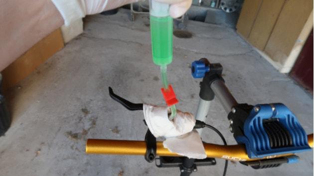 Le mécanicen repousse le piston de la seringue pour remplir le maître cylindre du frein hydraulique NUTT