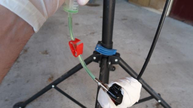 Mécanicien repoussant le piston de la seringue n°2 pour renvoyer du liquide frein VTT