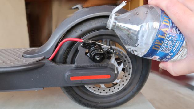 Rider nettoyant ses etriers de freins de trottinette électrique avec de l'eau