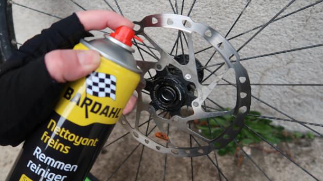Mécanicien mettant du spray nettoyant frein sur son disque vtt Shimano XT